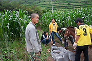 People load a stack of roof tiles onto baskets being carried by a horse near to Lugu Lake, Yunnan, China.