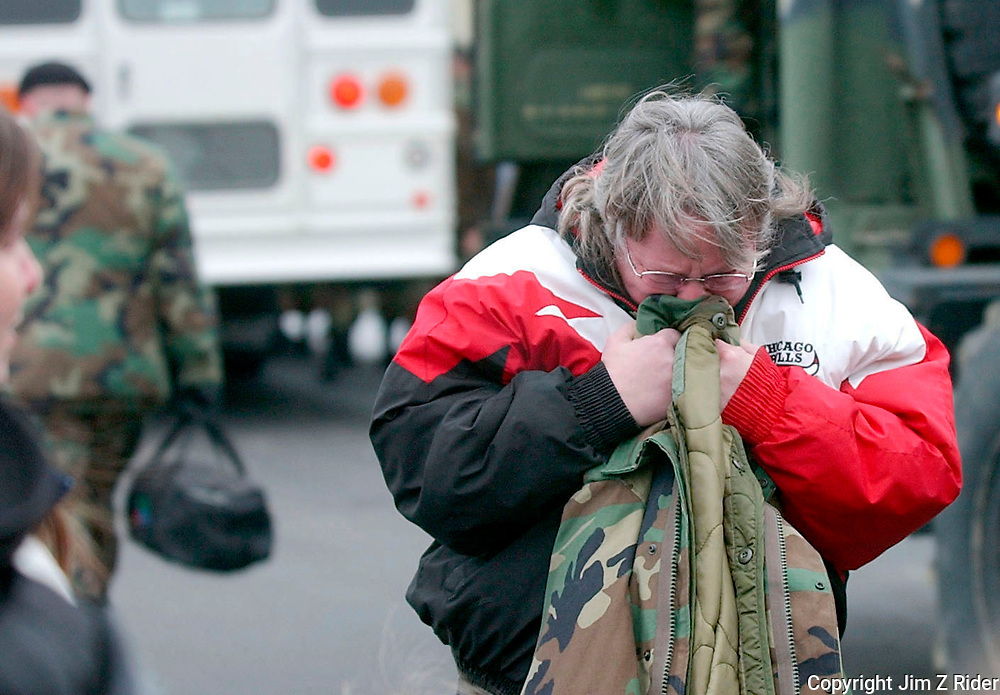 A woman clutches her husband's coat and weeps as he boards a bus at the Reserve Center in South Bend.  Members of the Indiana National Guard will report for active duty at Camp Atterbury in southern Indiana for further training and deployment to Iraq.