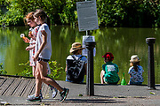 A mother and young children sit by one of the re-opened fishing ponds - People enjoy the sun on Clapham Common after the Government eased restrictions and allowed people to meet - Lambeth Council have replaced signs to say stay alert and to allow people sit on benches. The eased 'lockdown' continues for the Coronavirus (Covid 19) outbreak in London.