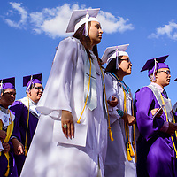 Lauren Smith, center, and other Miyamura High School graduates march into the stadium for their graduation Friday at Public School Stadium in Gallup.