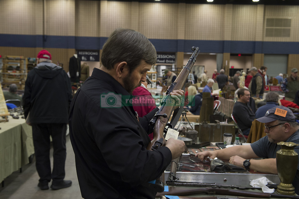February 4, 2018 - Dalton, GA - Military memorabilia and relics collectors gathered at Dalton Georgia exhibition center to buy, sell, trade swords, muskets, bullets and uniforms from 1800s to the Vietnam era. Military enthusiasts often spend thousands of dollars on their collections..Pictured: Collector examines WW2 era German Mauser K98 rifle. (Credit Image: © Robin Rayne Nelson via ZUMA Wire)