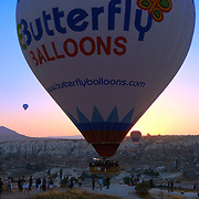 Big hot air balloon fly close to the hill with people, Cappadocia, Turkey