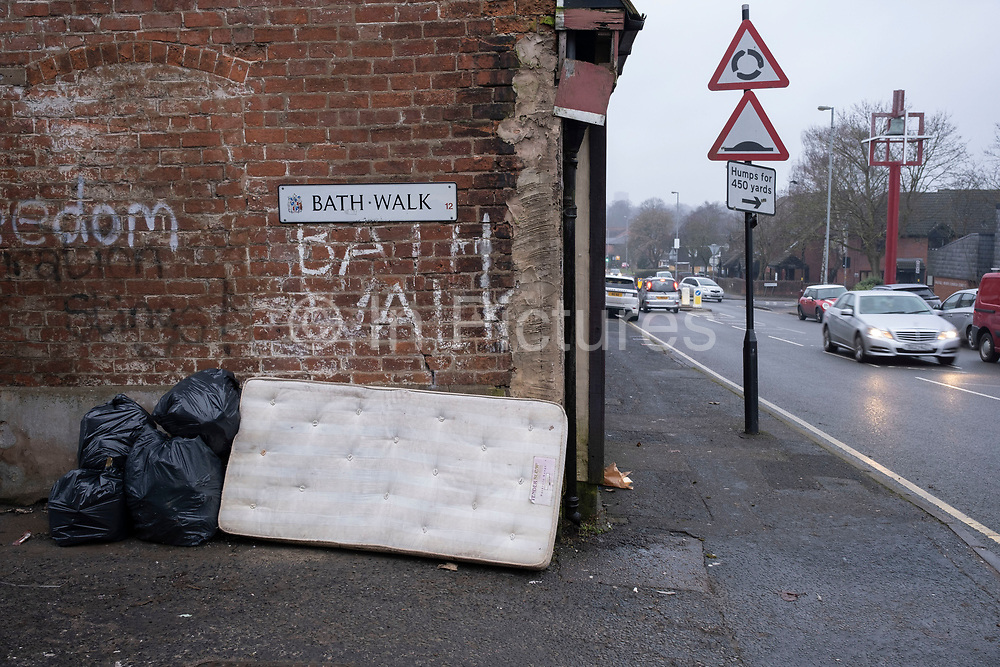 Old mattress is dumped on the street leaning against a brick wall in Balsall Heath on 18th January 2020 in Birmingham, United Kingdom. This sort of fly tipping is a common sight all over the city as unwanted or rubbish items are thrown away in public. Left for the council to clear up.