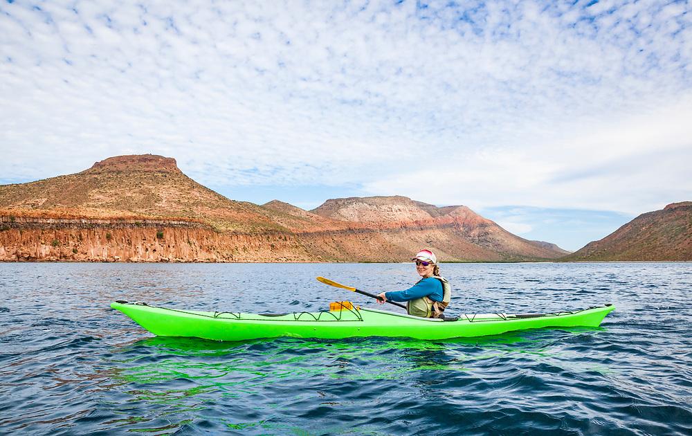 A woman sea kayaking off shore of  Isla Espirito Santo, Gulf of California, BCS, Mexico.