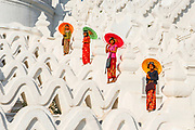Local female worshipers with parasols ascending the hsinbyume pagoda, Mingun, Myanmar