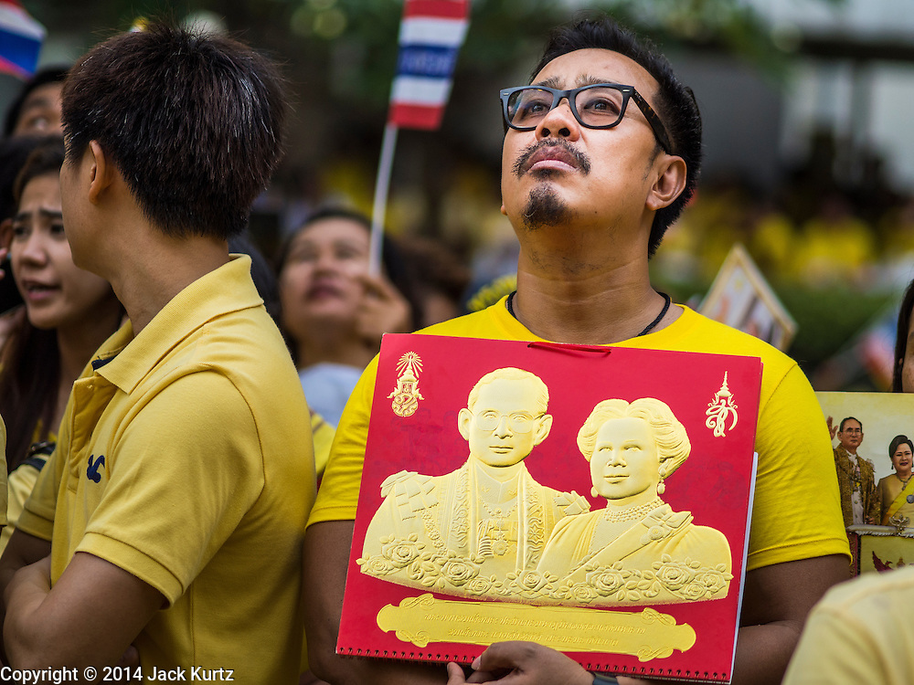 05 DECEMBER 2014 - BANGKOK, THAILAND: A Thai man holds an embossed portrait of the King and Queen of Thailand in the plaza of Siriraj Hospital. Thais marked the 87th birthday of Bhumibol Adulyadej, the King of Thailand, Friday. The revered Monarch was scheduled to make a rare public appearance in the Grand Palace but cancelled at the last minute on the instructions of his doctors. He has been hospitalized in Siriraj Hospital, across the Chao Phraya River from the Palace, since early October.    PHOTO BY JACK KURTZ