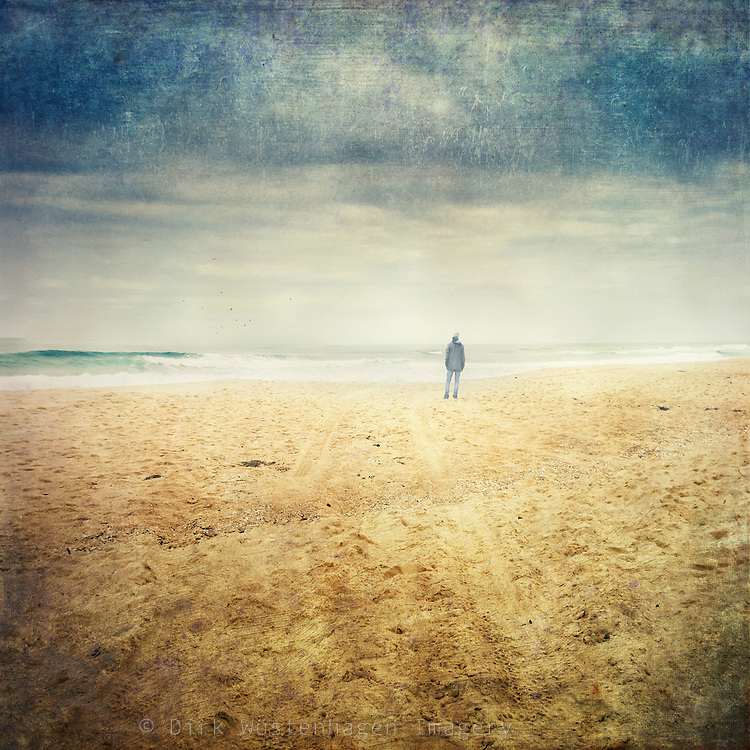Man standing on a beach, staring at the sea.<br /> textured photograph