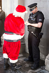 A police officer for Police Scotland has a quiet word with Ricky McConnell who dressed as Santa and waved at passeres by from the Duke of Wellington on the statue in Royal Exchange Square Glasgow<br />  21 December 2015<br />  Copyright Paul David Drabble<br />  www.pauldaviddrabble.co.uk