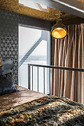 The hotel built inside a dockside CRANE ... where guests can enjoy a picnic in the top cabin<br /> <br /> This thrilling hotel in Harlingen, Netherlands, will provide a novel sleeping experience for guests if they have the head for heights to stay there.<br /> <br /> It is the second crane hotel to open in Holland, with guests bungee jumping off the top of its twin, the Faralda Crane Hotel in Amsterdam.<br /> <br /> A genuine dockside crane is converted here into a surprisingly luxurious getaway, or rather getup, with the old machine room transformed into a striking bedroom for two. <br /> <br /> They said it couldn't be done. And there were many hurdles that nearly prevented this mad concept from getting off the ground, but against the odds it succeeded. This then is a property of uncompromising character; a design hotel that pushed the boundaries of engineering to its limits.<br /> <br /> A spokesperson for the hotel said: 'This is a genuine dockside crane which has been the recipient of intelligent engineering and dedicated devotion rarely seen in a private home - let alone in a hotel property'.<br /> <br /> 'It is an out of this world property - staying here guarantees you stories to tell your friends'.<br /> <br /> The crane's flashy exterior – painted red, yellow and blue – is anything but subtle, but inside it's fascinatingly functional. There's no reception room or lounge and the lack of communal space means there are few opportunities for aesthetic assertions; the rickety lifts certainly aren't canvases for creative touches, but the suites they deliver you to are another story.<br /> <br /> All suites are equipped with the usual mod cons - coffee machines, kettles, minibars, televisions and music streaming devices - while wetrooms boast rainforest showers and porthole windows, which allow you to admire Amsterdam while conditioning your hair.<br /> <br /> Every room has spectacular views and because the crane moves in the wind guests often wake up with different vistas to the ones they had at bedtime. Suites from €435 (£371) per night, excluding b