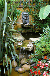 Water feature surrounded by strong foliage planting