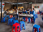 "12 FEBRUARY 2019 - SIHANOUKVILLE, CAMBODIA: Chinese construction workers eat dinner in one of the dining halls in a Chinese labor camp in Sihanoukville. There are about 50 Chinese casinos and resort hotels either open or under construction in Sihanoukville. The casinos are changing the city, once a sleepy port on Southeast Asia's ""backpacker trail"" into a booming city. The change is coming with a cost though. Many Cambodian residents of Sihanoukville  have lost their homes to make way for the casinos and the jobs are going to Chinese workers, brought in to build casinos and work in the casinos.      PHOTO BY JACK KURTZ"