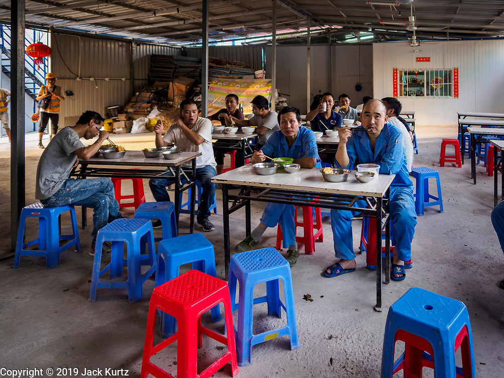 """12 FEBRUARY 2019 - SIHANOUKVILLE, CAMBODIA: Chinese construction workers eat dinner in one of the dining halls in a Chinese labor camp in Sihanoukville. There are about 50 Chinese casinos and resort hotels either open or under construction in Sihanoukville. The casinos are changing the city, once a sleepy port on Southeast Asia's """"backpacker trail"""" into a booming city. The change is coming with a cost though. Many Cambodian residents of Sihanoukville  have lost their homes to make way for the casinos and the jobs are going to Chinese workers, brought in to build casinos and work in the casinos.      PHOTO BY JACK KURTZ"""
