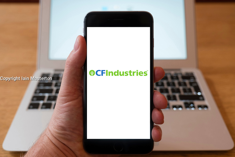 Using iPhone smartphone to display logo of CFIndustries; a manufacturer and distributor of agricultural fertilisers,