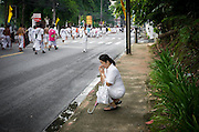 An onlooker pray during street procession. Onlookers can receive blessings from warriors during the procession. Every year during the ninth lunar month of the Chinese calendar, the Phuket Vegetarian Festival kicks off. The religious festival in Phuket, Thailand, lasts for 10 days, during which sacred rituals take place in the many Chinese shrines and temples. Walking on fire and climbing ladders with bladed rungs barefoot are two of several rituals believed to bring good fortune. The main purpose of the festival, however, is spiritual cleansing and merit-making.<br />Participants of the festival adhere to a strict vegetarian diet for at least three days. This is one of the 10 main rules meant to ensure good hygiene and inner peace. Sex, alcohol, and meat are strictly forbidden. As cleanliness is considered to be of paramount importance, menstruating and pregnant women are not supposed to attend any of the rituals. The festival rules also call for impeccable mental and physical behavior as well as white clothing.