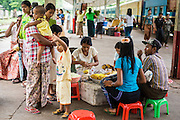 15 JUNE 2013 - YANGON, MYANMAR:  People buy snacks while they wait for the Circular Train in Yangon train station. Yangon Circular Railway is the local commuter rail network that serves the Yangon metropolitan area. Operated by Myanmar Railways, the 45.9-kilometre (28.5mi) 39-station loop system connects satellite towns and suburban areas to the city. The railway has about 200 coaches, runs 20 times and sells 100,000 to 150,000 tickets daily. The loop, which takes about three hours to complete, is a popular for tourists to see a cross section of life in Yangon. The trains from 3:45 am to 10:15 pm daily. The cost of a ticket for a distance of 15 miles is ten kyats (~nine US cents), and that for over 15 miles is twenty kyats (~18 US cents). Foreigners pay 1 USD (Kyat not accepted), regardless of the length of the journey.     PHOTO BY JACK KURTZ