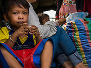 16 JUNE 2014 - POIPET, CAMBODIA: A Cambodian child waits in the back of an army truck to go home. He was one of thousands of Cambodian migrants who returned to Cambodia from Thailand Monday. More than 150,000 Cambodian migrant workers and their families have left Thailand since June 12. The exodus started when rumors circulated in the Cambodian migrant community that the Thai junta was going to crack down on undocumented workers. About 40,000 Cambodians were expected to return to Cambodia today. The mass exodus has stressed resources on both sides of the Thai/Cambodian border. The Cambodian town of Poipet has been over run with returning migrants. On the Thai side, in Aranyaprathet, the bus and train station has been flooded with Cambodians taking all of their possessions back to Cambodia.  PHOTO BY JACK KURTZ