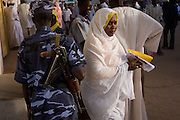 Under the watchful eye of a Sudanese policeman armed with an Kalashikov AK-47, a lady delegate attending the first-ever international Conference on Womens' Challenge in Darfur, leaves the compound belonging to the Govenor of North Darfur in Al Fasher (also spelled, Al-Fashir) where the women from remote parts of Sudan gathered to discuss peace and political issues.