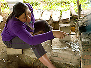 Ms Vanthone, metalworker casting bracelets made from recycled aluminium sourced from Vietnam War debris and melted in an earthen kiln in Ban Naphia, a remote Tai Phouan village in mountainous Xieng Khouang Province in Northern Laos. Laos is the most bombed country, per capita, in the world with more than two million tons of ordnance dropped on it during the Vietnam War from 1963 to 1974.12 artisan families began transforming war scrap into spoons (150,000 per year) in the 1970s to supplement subsistence farming activities. Supported by the Swiss NGO Helvetas, the project works to make the scrap metal supply chain safer for artisans and scrap collectors by collaborating with organisations such as Mines Advisory Group (MAG) that specialise in unexploded ordnance removal and education. More recently the villagers have started making bracelets and other items.