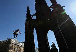 Manu Tigher, a comedy acrobat, performs in front of the Scott Monument in Princes Street Gardens, Edinburgh, during the 2017 Edinburgh Fringe Festival.