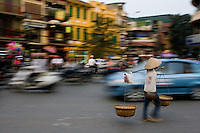 A woman wearing a conical hat with baskets hanging poles wanders along the streets.