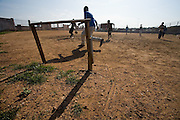 Children playing football on dirt field, Accra, Ghana, 2006.