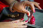 23 NOVEMBER 2013 - BANGKOK, THAILAND: A member of the cast of the Prathom Bunteung Silp mor lam troupe puts on her nail polish before a performance in Bangkok. Mor Lam is a traditional Lao form of song in Laos and Isan (northeast Thailand). It is sometimes compared to American country music, song usually revolve around unrequited love, mor lam and the complexities of rural life. Mor Lam shows are an important part of festivals and fairs in rural Thailand. Mor lam has become very popular in Isan migrant communities in Bangkok. Once performed by bands and singers, live performances are now spectacles, involving several singers, a dance troupe and comedians. The dancers (or hang khreuang) in particular often wear fancy costumes, and singers go through several costume changes in the course of a performance. Prathom Bunteung Silp is one of the best known Mor Lam troupes in Thailand with more than 250 performers and a total crew of almost 300 people. The troupe has been performing for more 55 years. It forms every August and performs through June then breaks for the rainy season.              PHOTO BY JACK KURTZ