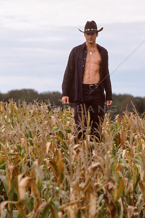 cowboy standing in a corn field with an open shirt
