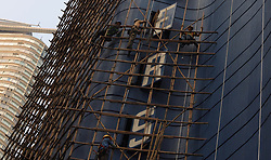 October 9, 2018 - Hong Kong, CHINA - Bamboo scaffolding engineers construct a bamboo scaffolding along the outer wall of an old hotel awaiting to be demolished. Hong Kong preserve classic skill of bamboo scaffoldings as a heritage of Chinese traditional architectural craft. Oct-9,2018 Hong Kong.ZUMA/Liau Chung-ren (Credit Image: © Liau Chung-ren/ZUMA Wire)