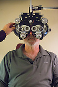 Owner Raymond Pedersen, OD, examines Fremont resident Rick Reisinger's eyes with a phoropter at Capitol Eye Care Center in Fremont, California, on April 10, 2014. Pedersen has been in business since 1987. (Stan Olszewski/SOSKIphoto)