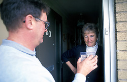 Council worker showing ID to householder at front door UK