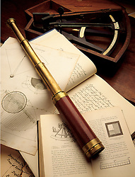Antique telescope or spyglass on navigation books with octant in background
