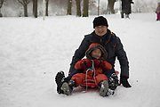People in Kings Heath Park head out to enjoy the heavy snow fall and do some sledging on Sunday 10th December 2017 in Birmingham, United Kingdom. Deep snow arrived in much of the UK, closing roads and making driving treacherous, while many people simply enjoyed the weather.