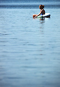 A young girl floats in a swim tube on Lake Megunticook, Camden, Maine