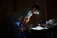 As the sun drops behind the mountains, nurse Daniel Danilczyk uses a headlamp to search for medical supplies for the Himalayan Family Healthcare Project medical camp in Tilche, Nepal. The medical professionals mostly worked without electricity in the camps.