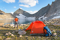 Noel Lake backcountry camp with adult male backpacker in red shirt enjoying the view. Bridger Wilderness. Wind River Range, Wyoming