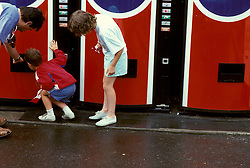 Family looks for soft drinks in vending machines. CITY URBAN STOCK PHOTO