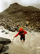 Mareile crosses a stream with ice in it while the snow falls.<br /> Going over the 4925m Irshad Uween pass, the border between Afghanistan and Pakistan, in our last days trekking.<br /> <br /> Adventure through the Afghan Pamir mountains, among the Afghan Kyrgyz and into Pakistan's Karakoram mountains. July/August 2005. Afghanistan / Pakistan.