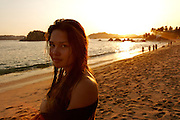 A pretty russian girl in a public beach of Acapulco,  a world famous international destination for vacation in Mexico,  during the sunset.