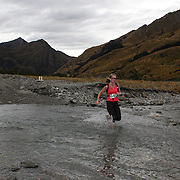 Runner Susan Slee crosses  Moke Creek on the Ben Lomond High Country Station during the Pure South Shotover Moonlight Mountain Marathon and trail runs. Moke Lake, Queenstown, New Zealand. 4th February 2012. Photo Tim Clayton