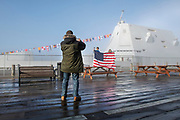 Rodger Wilson takes a photo through the fog of Tade Shores, 9, and Tate Shores, 7, while in front of the Navy destroyer USS Zumwalt on the morning of March 3, 2019 at Berth 2 in Kecthikan, Alaska.