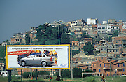 CAR ADVERTISEMENT. Rocinha Favela, Rio de Janeiro, Brazil, South America. Favela and advertisement for car. Although Rocinha is technically classified as a neighborhood, many still refer to it as a favela. It developed from a shanty town into an urbanized slum. Today, almost all the houses in Rocinha are made from concrete and brick. Some buildings are three and four stories tall and almost all houses have basic sanitation, plumbing, and electricity. Compared to simple shanty towns or slums, Rocinha has a better developed infrastructure and hundreds of businesses. There is also lots of deliquency, crime and drugs in the favelas.