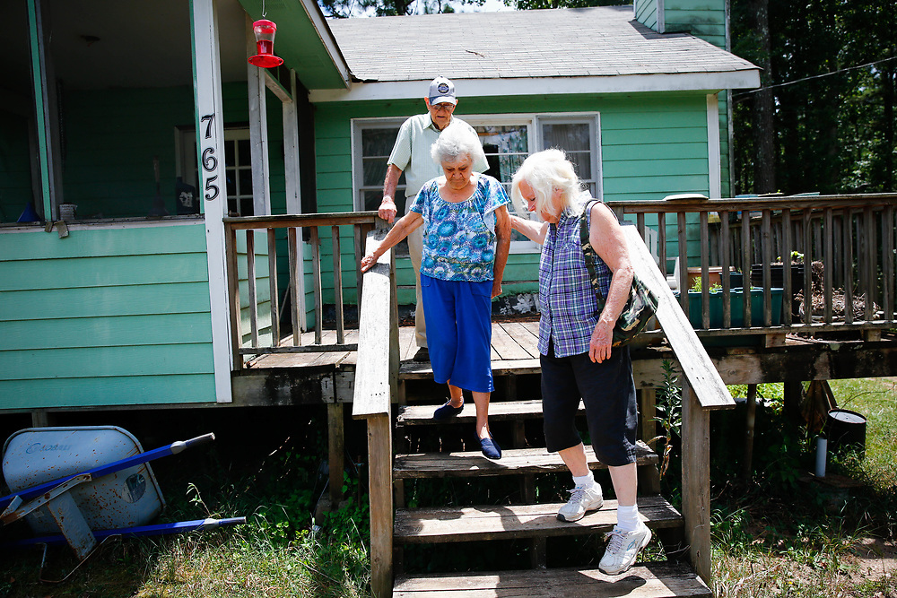 """Jo Ann Sparks helps her mother, Sara Cook, down the stairs at Ms. Cook's home in Greenville, Ga., on Thursday, July 28, 2106. Also pictured is James Cook, Ms. Sparks' father and Ms. Cook's husband (who lives there with her). Ms. Cook, who is 86, suffers from dementia.<br /> <br /> In 1990, Ms. Cook purchased a Transamerica life insurance policy with a value of $100,000. Late last year, after paying more than $55,000 in premiums, the couple received a letter saying that their premiums were going up 38 percent. When Ms. Sparks, who takes care of the couple, showed the letter to an insurance analyst, he said, """"Please don't take this the wrong way and not to be morbid, but your mother needs to die."""" So the couple decided earlier this year to surrender the policy and collect $4,100 for it. That's enough, her mother figures, to cover the costs of her eventual funeral.<br /> <br /> Photo by Kevin D. Liles for The New York Times"""