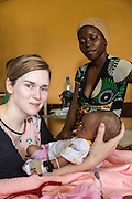 VSO volunteer Dr Siobhan Neville who specialise in paediatrics with 1 month old Fatiha and her mother Zabibu on the children's ward. St Walburg's Hospital, Nyangao. Lindi Region, Tanzania.
