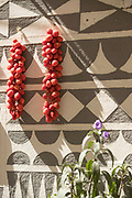 Tomatoes drying on wall of house decorated in traditional patterns, Pyrgi, Chios, Greece