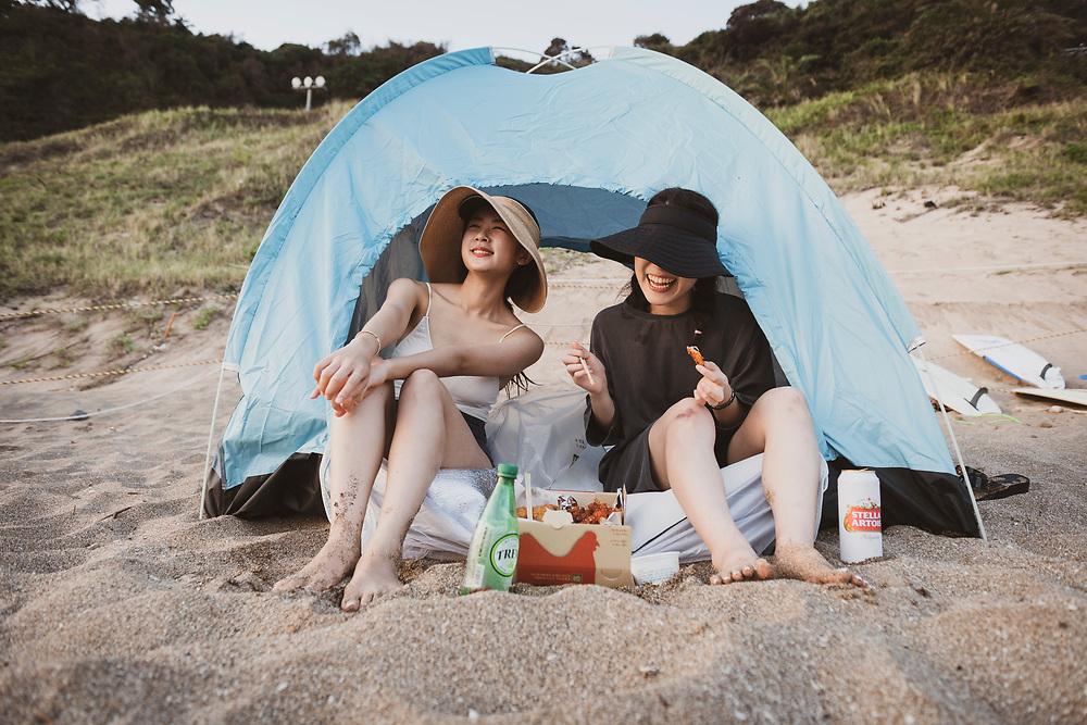 Jeju Island, South Korea - September 15, 2019: Su Yeong Kang and Ji Hyeon Kim enjoy an evening meal of chicken at Jungmun Beach on Jeju Island, South Korea.