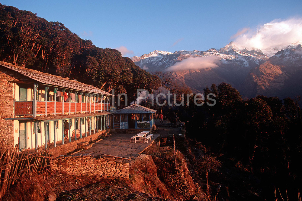 A dawn landscape of a mountain hostel at Ghorepani in the Annapurna Sanctuary, a preservation area of Nepal, high in the Himalayan foothills, on 16th January 1997, in Ghorepani, Nepal. Villages like this partly-depend on the agriculture of rice-growing and also on the passing tourist trade. Western trekkers walk through these tiny communities on their way up the series of climbing trails of the Annapurna Conservation Sanctuary circuit, a sometimes rigorous walk from the low hills of Pokhara to the higher altitudes of Annapurna, the 26,000 feet 8,000 metre peak.
