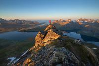Male hiker overlooks mountain landscape of Selfjord area from summit of Kitind, Moskenesøy, Lofoten Islands, Norway