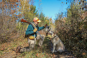 Hunter Ruffed grouse hunting with a Yellow Labrador Retriever