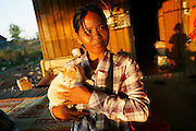 Touth Koeun, with a cat in the Dangrek mountains..Touth Koeun, an ex-Khmer Rouge child soldier turned midwife and trainer, is on the frontline again, but this time campaigning on maternity issues, in Preah Vihear province, Cambodia. The country experiences an extraordinarily high incidence of infant and maternal mortality. The Preah Vihear province, in Cambodia's north, bordering on the Thai border, can be described as an outback rural area, villages often many hours away from a health centre or clinic, and sometimes near the frontline where soldiers and their families are living. Here, Touth Kouen, a locally much respected pioneer and experienced in maternity issues, trains indigenous women, known as 'Traditional Birth Attendants' (TBA's), correct procedures to assist midwives and nurses, to give direct support to mothers and their babies, during ante and post natal periods. Traditional bush medicine and spiritual practices by 'Kruu' bush doctors, involving the killing of endangered species, gathering herbs and plants, whose burnt remains are often ground up into unhealthy potions, and fed to mothers as miracle cures, and postpartum heating, can cause illness and death. The Kruu, and local people in general need to be re-educated, so as to create a healthy nurturing environment for mothers and their babies. Preah Vihear Province, Cambodi