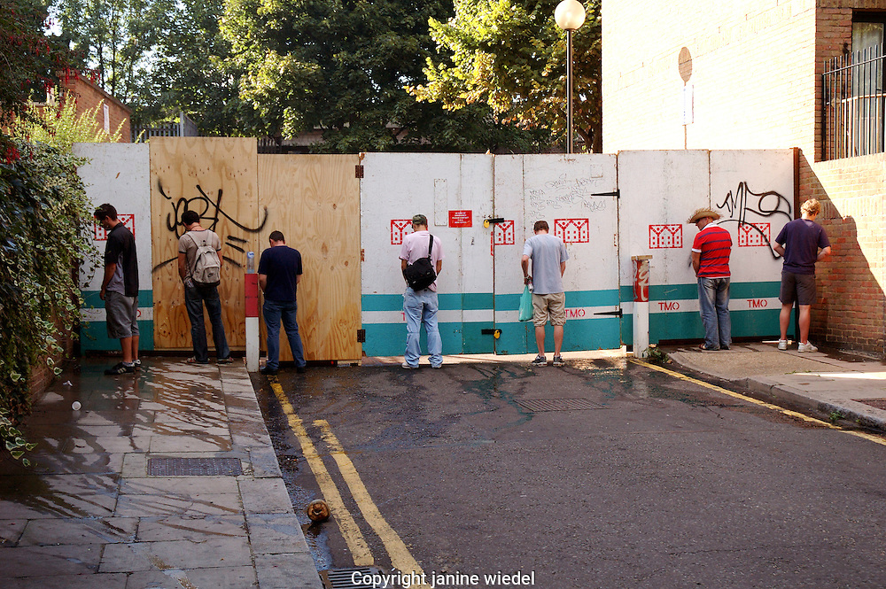 Men urinating against hoardings in West london at Notting hill carnival time.